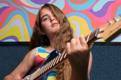 Girl playing guitar with funky painting - stock photo
