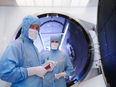 Workers with satellite testing chamber - stock photo