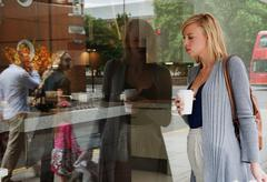 Woman looking in shop window Stock Photos