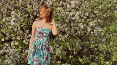 Girl in a dress smiling near blossoming tree Stock Footage