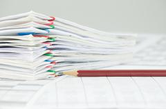 Brown pencil and overload of paperwork on white background - stock photo