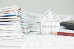 House with pencil and overload of paperwork on finance account Stock Photos