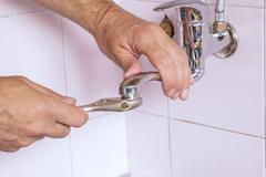 Plumber fixing the tap - stock photo
