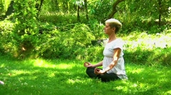 Attractive young women meditating in nature Stock Footage