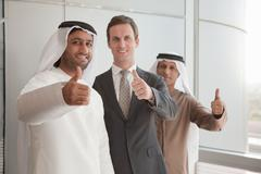 Middle eastern and western businessmen giving thumbs up - stock photo