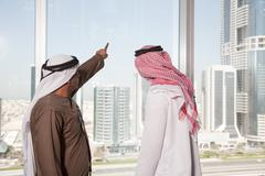 Middle eastern businessmen looking at dubai through office window - stock photo