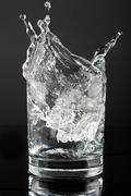 Ice cube splashing in a tumbler of gin and tonic - stock photo