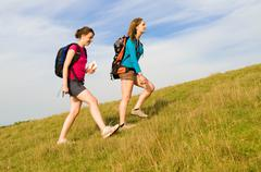 Two hikers climb hill - stock photo