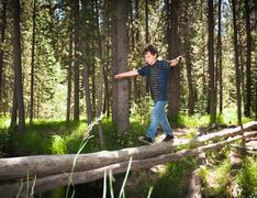 Boy walking across log Stock Photos