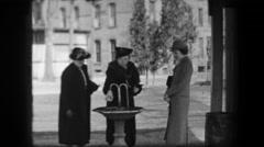 1938: Women filling water bottles from public fountain in formal period dress. Stock Footage
