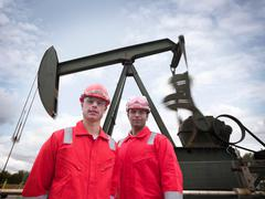 Two workers looking to camera, in front of onshore oil well pump (nodding - stock photo