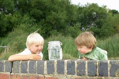 Two young boys looking at fish in a jar - stock photo