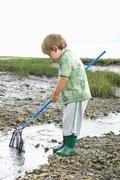 Young boy fishing with net - stock photo