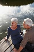 Senior couple flirting on jetty Stock Photos