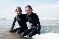 Children sitting on surf board in the se - stock photo