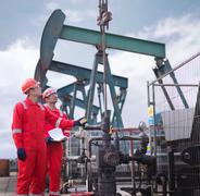 Two workers taking a reading and looking up, next to oil pumps above onshore oil Stock Photos