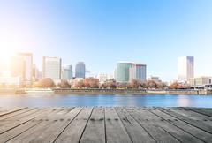 Empty wood floor near water with cityscape and skyline of portland Stock Photos