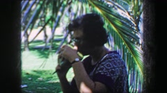 1967: Woman drinking freshly cracked coconut water straight from fruit. JUPITER, Stock Footage