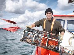 Fisherman with lobster pot and crabs - stock photo