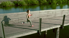 Young woman runs on a bridge aerial drone Stock Footage