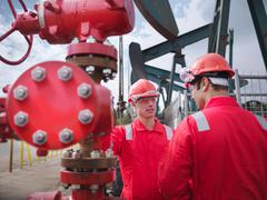 Workers talking next to 'christmas tree' at oil well pumps (nodding - stock photo