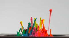 Streams of neon paint splash up from a speaker in slow motion, isolated on white Stock Footage
