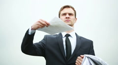 businessman standing with a stack of paper in the wind. throwing documents - stock footage