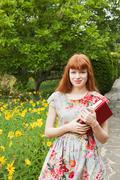 Young woman holding books in parkgarden - stock photo