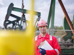 Worker looking to camera, carrying clipboard. In the background are oil pumps Stock Photos