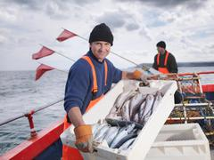 Fishermen on boat with catch of fish - stock photo