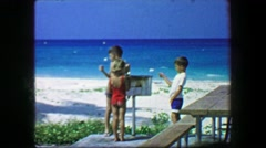 1967: Kids roasting marshmallows on beach grill white powder fine grain sand. Stock Footage