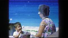 1967: Mother supervising marshmallow kid windy summer beach head veil. JUPITER, Stock Footage
