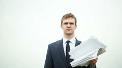 businessman standing with a stack of paper in the wind. - stock footage
