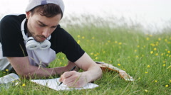 4K Casual man writing on a notepad in a meadow, in slow motion Stock Footage