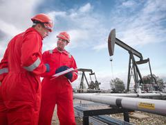 Two workers looking at a clipboard in the foreground with onshore oil pumps Stock Photos