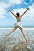 Girl leaps on waters edge Stock Photos