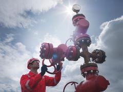 Worker turning valve on oil well 'christmas tree', looking up Stock Photos