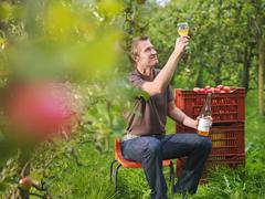 Farmer drinking cider in orchard - stock photo