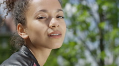 Close up portrait of young african american girl relaxing in sunny park. Stock Footage