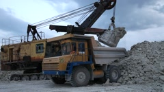 Excavator loads a truck rock in the quarry Stock Footage