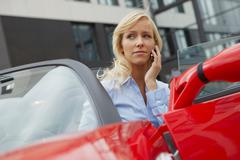 Women on phone in her electric car Stock Photos