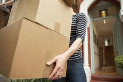 Woman carrying brown boxes from house Stock Photos