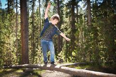 Boy walking across log Stock Photos