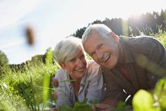 Senior couple lying in meadows smiling Stock Photos