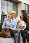 Two business women having take away food - stock photo