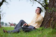 Young man with i-pad and mobile phone Stock Photos