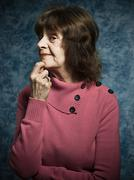 Suspicious senior woman with hand on chin - stock photo
