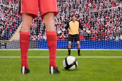 Goalkeeper anticipating free kick - stock photo