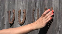 Country woman hand hang old rusty horseshoes on old wooden door - symbol of luck Stock Footage