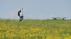 4K Young male walks in a meadow holding a musical instrument, in slow motion - stock footage